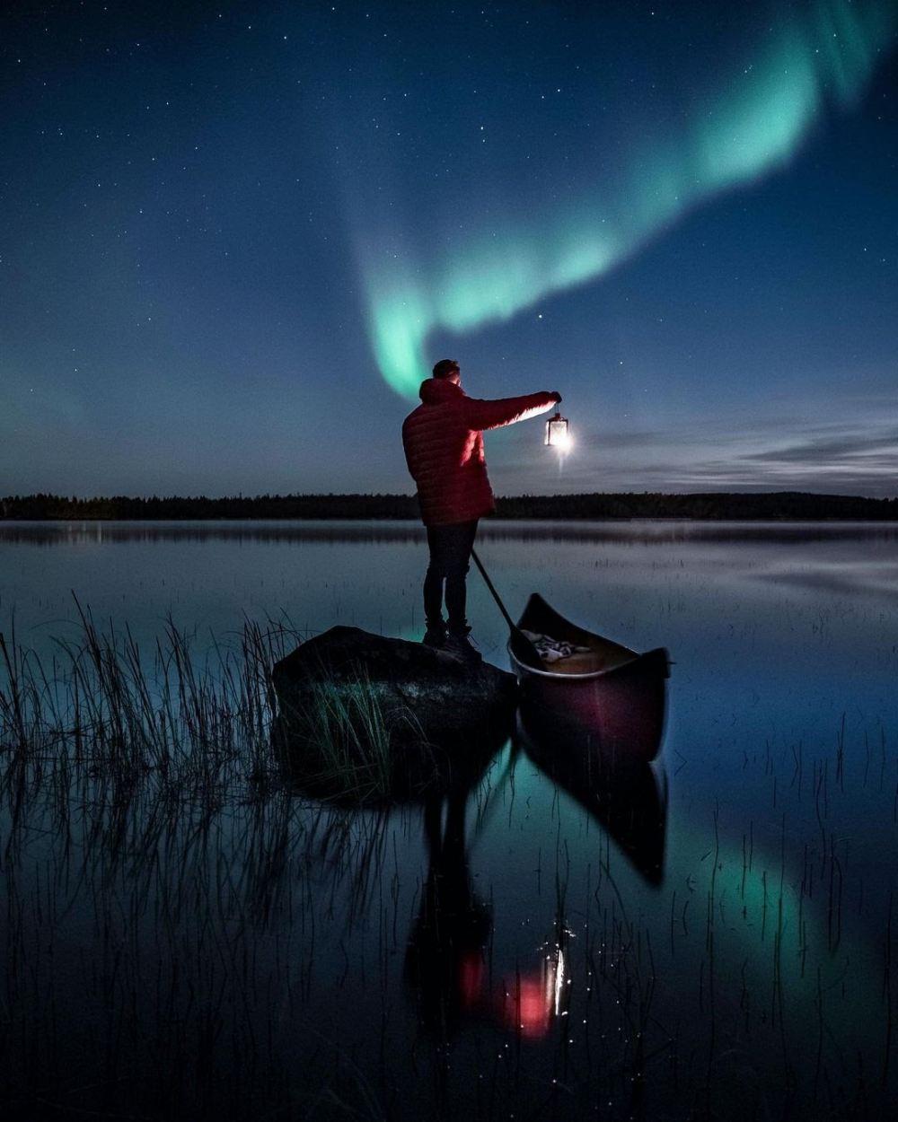 standing man on a small boat and the northern lights - 带上你最爱的人到芬兰Rovaniemi看浪漫的北极光!